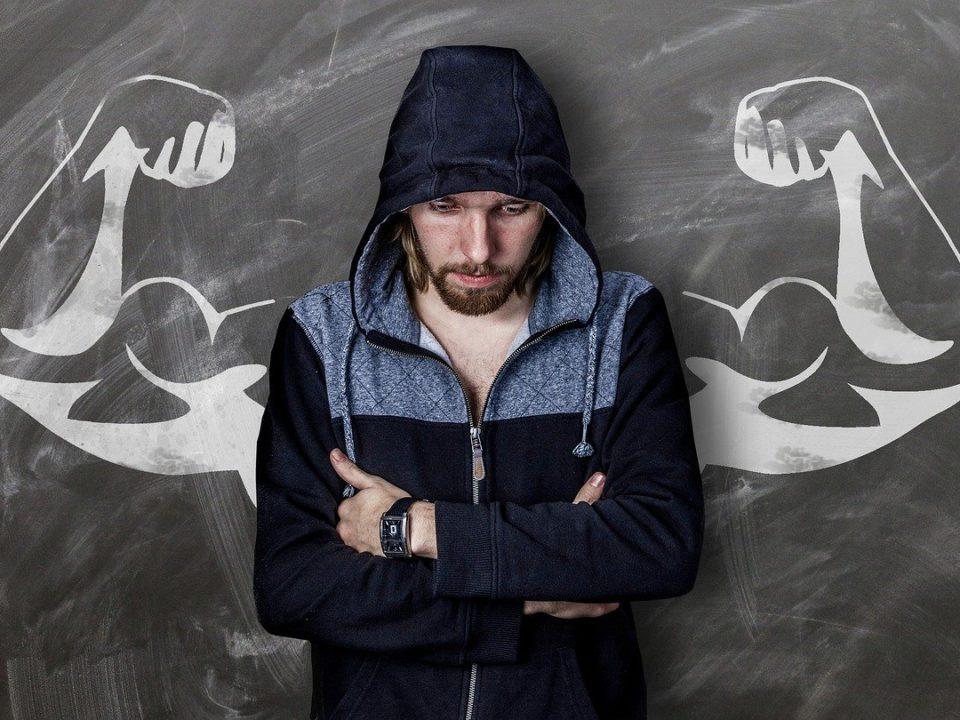 szczupły mężczyzna w bluzie dresowej na tle mocarnych ramion