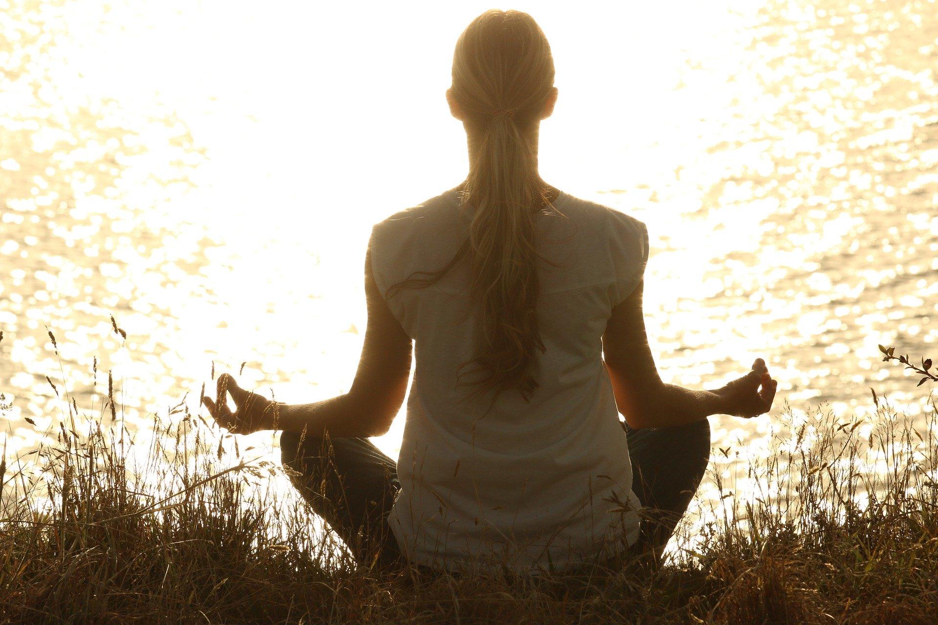 kobieta medytuje nad jeziorem