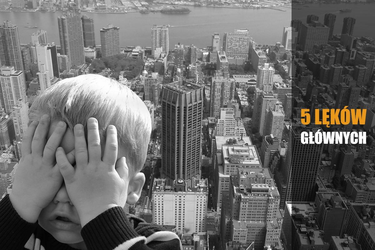 Dziecka z zasłania rączkami oczy w obawie przed lękiem wysokości. W tle panorama miasta widziana z wysokości.